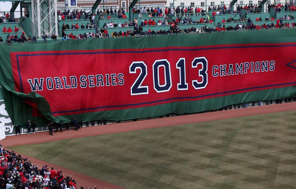 One by one, banners commemorating the 2004, 2007, and 2013 championships were unfurled on the Green Monster, with last year's covering up the other two.
